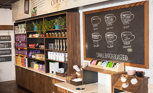 Interior view of a PJ's Coffee store with chalkboard and items station