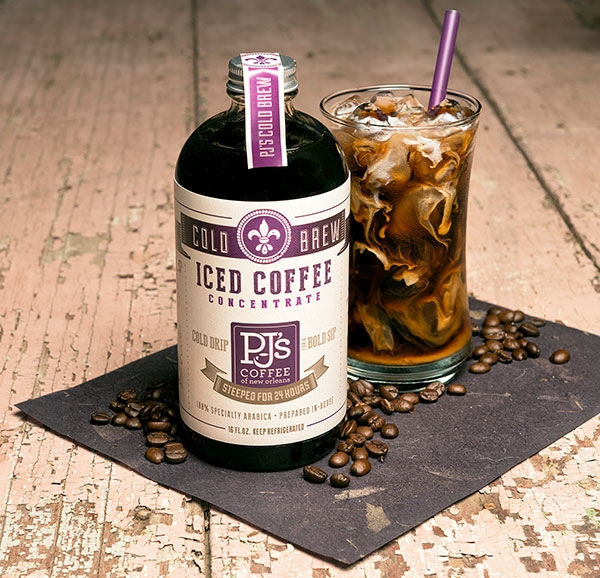 Iced Coffee Concentrate bottle shown with coffee beans on table